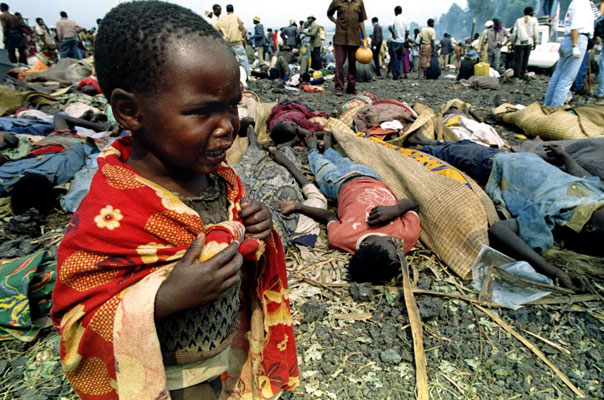 A Rwandan child cries next to his dead parents' bodies (background) at a refugee camp, 10 kilometres outside Goma, Zaire, July 21, 1994. Thousands of exhausted Hutu refugees fleeing Tutsi troops ended up in this camp, only to succumb to a cholera epidemic. The child was later picked up and sent to an orphanage. © Jack Dabaghian